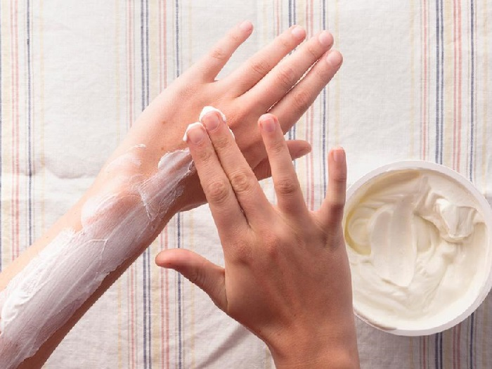 Нанесение сметаны на кожу рук