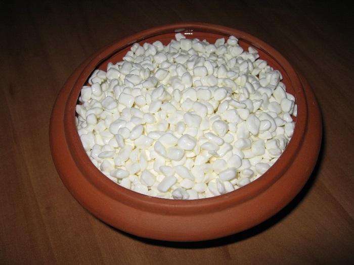 Изображение творожного зерна в деревянной тарелке